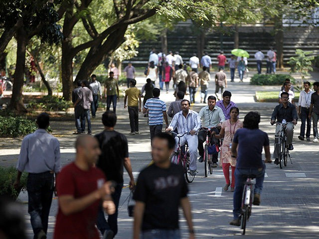 FILE- In this Jan. 11, 2013 file photo, Infosys Technologies employees move through the headquarters during a break in Bangalore, India. The shares of top Indian IT companies are falling in response to news of proposed U.S. legislation that would require salaries for H-1B visa holders to be doubled to …