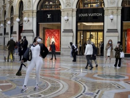 Tourists wearing face masks pose and take photos at the Vittorio Emanuele Gallery shopping arcade, in Milan, Italy, Friday, Feb. 28, 2020. Authorities have decided to re-open schools and museums in some of the less areas less hard-hit by the coronavirus outbreak, in which Italy has the most cases outside …