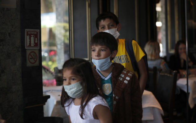 A trio of cousins wear medical masks as a precaution against the spread of the new coronavirus, during an outing to a restaurant in Mexico City, Saturday, Feb. 29, 2020. Mexico's Health Department said late Friday that a new case had been confirmed in Mexico City, adding to the first …