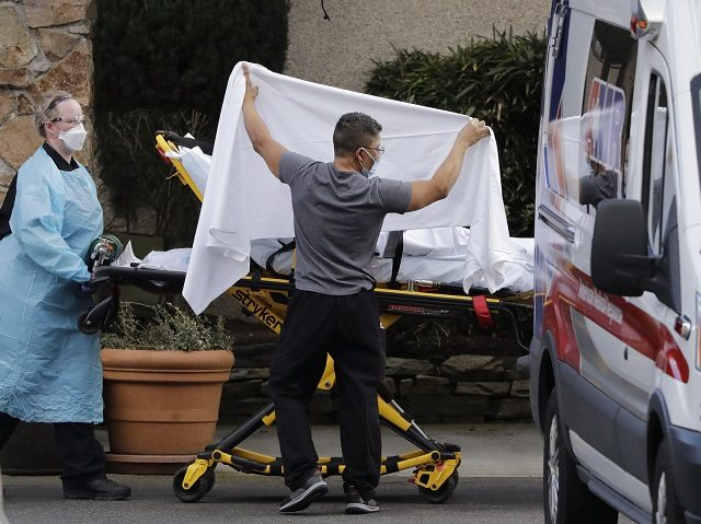 In this Feb. 29, 2020, file photo, a staff member blocks the view as a person is taken by a stretcher to a waiting ambulance from a nursing facility where more than 50 people are sick and being tested for the COVID-19 virus, in Kirkland, Wash. News organizations must walk …