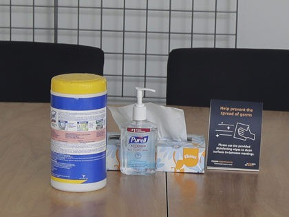 Hand sanitizer, cleaning wipes, and tissues sit on a meeting room table as seen through a window of the Brazil Building on Amazon's Seattle campus, Wednesday, March 4, 2020, in Seattle. On Tuesday, an Amazon spokesperson said an employee who worked in the building had tested positive for the COVID-19 …