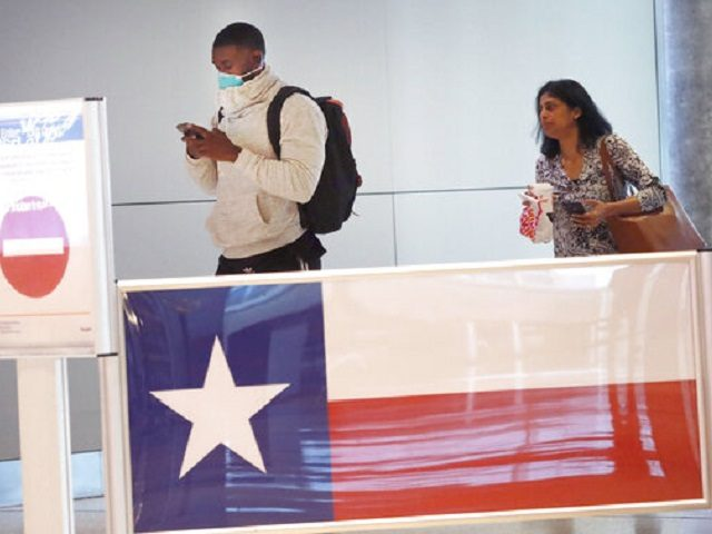 Travelers make their way through Love Field airport in Dallas, Thursday, March 12, 2020. (AP Photo/LM Otero)