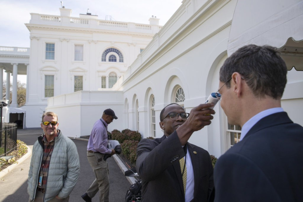 A member of the media, right, gets their temperature taken by member of the White House physicians office, over concerns about the coronavirus outside the James Brady Briefing Room at the White House, Saturday, March 14, 2020, in Washington. The White House announced Saturday that it is now conducting temperature checks on anyone who is in close contact with President Donald Trump and Vice President Mike Pence. The vast majority of people recover from the new coronavirus. According to the World Health Organization, most people recover in about two to six weeks, depending on the severity of the illness.(AP Photo/Alex Brandon)