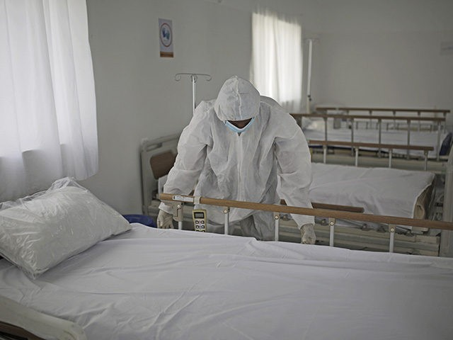 A medical staff member adjusts the sheets on a bed as personnel setup a coronavirus quarantine ward at a hospital in Sanaa, Yemen, Sunday, March 15, 2020. (AP Photo/Hani Mohammed)