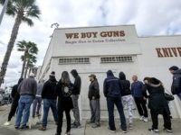 People wait in a line to enter a gun store in Culver City, Calif., Sunday, March 15, 2020. Coronavirus concerns have led to consumer panic buying of grocery staples and now gun stores are seeing a run on weapons and ammunition as panic intensifies. (AP Photo/Ringo H.W. Chiu)