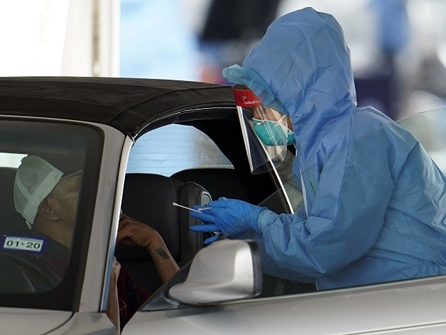A patient is tested by a healthcare professional at a drive-thru testing site for COVID-19 at United Memorial Medical Center Thursday, March 19, 2020, in Houston. For most people, the coronavirus causes only mild or moderate symptoms, such as fever and cough. For some, especially older adults and people with …