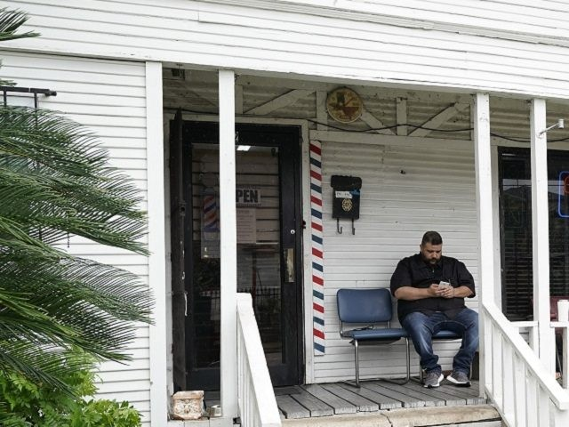 Barber Carlos Vasquez sits on the porch of his family's barber shop as he waits for a customer Friday, March 20, 2020, in Houston. Vasquez estimates their business has dropped in half since the coronavirus outbreak. (AP Photo/David J. Phillip)