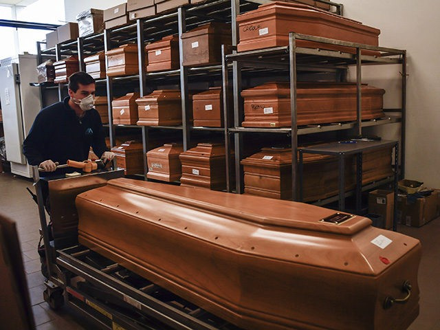 A worker takes away a coffin in the Crematorium Temple of Piacenza, Northern Italy, saturated with corpses awaiting cremation due to the coronavirus emergency Monday, March 23, 2020. For most people, the new coronavirus causes only mild or moderate symptoms. For some it can cause more severe illness, especially in …
