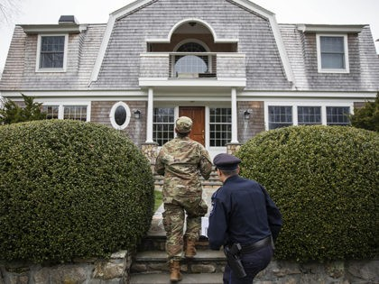 Rhode Island Air National Guard Tsgt. William Randall, left, and Westerly police officer Howard Mills approach a home while looking for New York license plates in driveways to inform them of self quarantine orders, Saturday, March 28, 2020, in Westerly, R.I. States are pulling back the welcome mat for travelers …