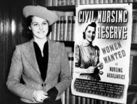 As part of a campaign to enroll 10,000 young women volunteers for Britain's civil nursing reserve, which will operate emergency hospitals in the event of war, posters such as this appeared throughout Great Britain, on April 27. Miss Greta Berry, the model of the poster nurse, is beside one of …