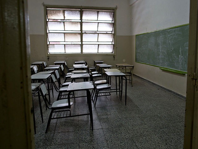 Desks sit empty in a public school classroom in a Buenos Aires suburb, Argentina, Wednesday, March 19, 2014. Striking teachers in the Buenos Aires province are demanding a wage increase higher than what is currently being offered by the provincial administration. The strike is in its 11th day, affecting more …