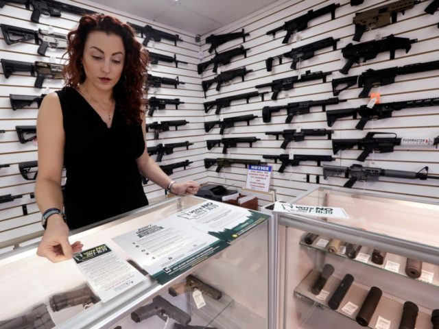 In this photo taken Tuesday, Oct. 2, 2018, gun shop owner Tiffany Teasdale stands with walls of semi-automatic rifles behind and counters filled with pistols as she talks about a gun initiative on the upcoming ballot, in Lynnwood, Wash. Voters in Washington state will decide the fate of Initiative 1639, …
