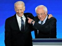 Former US vice president Joe Biden, left, embraces Sen. Bernie Sanders during a Democratic presidential primary debate, February 7, 2020, hosted by ABC News, Apple News, and WMUR-TV at Saint Anselm College in Manchester, New Hampshire. (AP Photo/Elise Amendola)