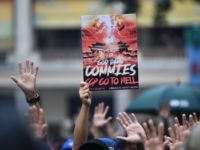 "A protester holds up a placard that reads ""God damn commies, CCP (Chinese Communist Party) go to hell"" as others hold up their hands to signify their five demands at a rally in the Wanchai district of Hong Kong on October 1, 2019, as the city observes the National Day …"