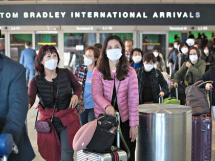 Passengers wear protective masks at Los Angeles international airport. New Zealand is seeking to bring back affected residents from Wuhan on a chartered Air New Zealand flight. Photograph: Mark Ralston/AFP via Getty Images