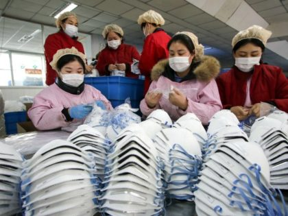 TOPSHOT - This photo taken on January 22, 2020 shows workers producing facemasks at a factory in Handan in China's northern Hebei province. - China banned trains and planes from leaving Wuhan at the centre of a virus outbreak on January 23, seeking to seal off its 11 million people …