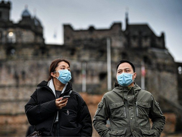 EDINBURGH, SCOTLAND - JANUARY 24: Tourists wear face masks as they visit Edinburgh Castle on January 24, 2020 in Edinburgh, Scotland. It has been confirmed that 14 people in Scotland with symptoms have tested negative for the coronavirus, which has killed at least 26 people in China. A daily incident …