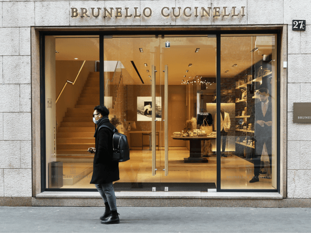 MILAN, ITALY - FEBRUARY 29: A man wears a protective mask as he walks in front of the Bruno Cucinelli store in Via Montenapoleone, the most important road of the fashion district in the city center where all the luxury brand are located on February 29, 2020 in Milan, Italy. …