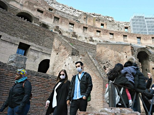 Tourists wearing respiratory masks visit the Coliseum in Rome on March 6, 2020. - Italy on March 5 reported 41 new deaths from the novel coronavirus, its highest single-day total to date, bringing the number of fatalities in Europe's most affected country to 148. All of Italy's 22 regions have …