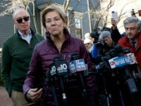 Sen. Elizabeth Warren, D-Mass., with her husband Bruce Mann beside her, speaks to the media outside her home, Thursday, March 5, 2020, in Cambridge, Mass., after she dropped out of the Democratic presidential race. (AP Photo/Steven Senne)
