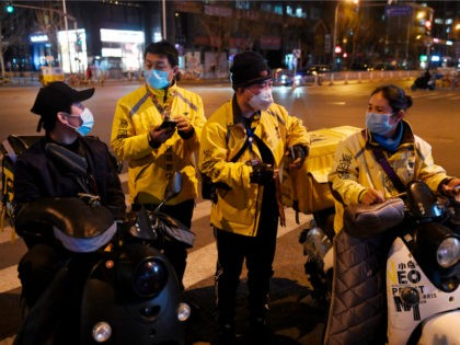 Food delivery riders wearing facemasks amid concerns over the spread of the COVID-19 novel coronavirus, wait for delivery assignments outside a restaurant in Beijing on March 20, 2020. (Photo by GREG BAKER / AFP) (Photo by GREG BAKER/AFP via Getty Images)