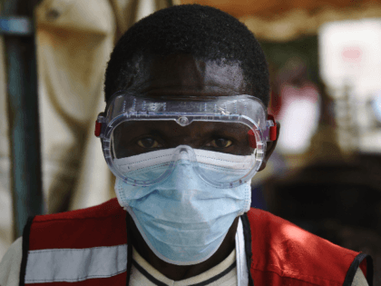 A health worker wears protective gears at the Mpondwe Health Screening Facility in the Uganda border town with the Democratic Republic of Congo, on June 13, 2019. - A grandmother in Uganda has died from Ebola, health officials said on June 12, 2019, the second fatality in the country since …