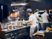 the team of cooks backs in the work in the modern kitchen, the workflow of the restaurant in the kitchen. Copy space for text.