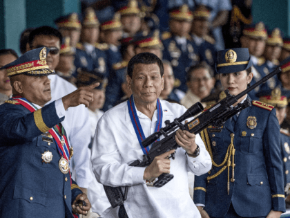 This file photo taken on April 19, 2018 shows Philippine President Rodrigo Duterte holding a Galil sniper rifle with outgoing Philippine National Police (PNP) chief Ronald dela Rosa (L) during the change of command ceremony at Camp Crame in Manila. - Philippine President Rodrigo Duterte fired Vice President and arch-critic …