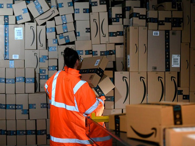 An employee places packed goods tons container at the distribution center of US online retail giant Amazon in Moenchengladbach, on December 17, 2019. (Photo by INA FASSBENDER / AFP) (Photo by INA FASSBENDER/AFP via Getty Images)