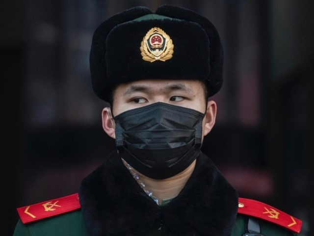 BEIJING, CHINA - JANUARY 22: A Chinese police officer wears a protective mask as he stands guard at Beijing Station before the annual Spring Festival on January 22, 2020 in Beijing, China. The number of cases of a deadly new coronavirus rose to over 400 in mainland China Wednesday as …