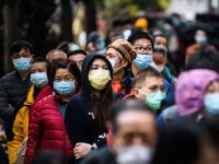 TOPSHOT - People wearing facemasks as a preventative measure following a coronavirus outbreak which began in the Chinese city of Wuhan, line up to purchase face masks from a makeshift stall after queueing for hours following a registration process during which they were given a pre-sales ticket, in Hong Kong …