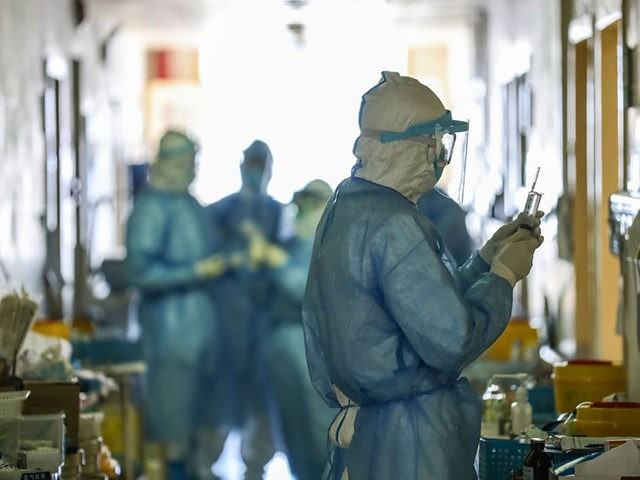 This photo taken on February 16, 2020 shows medical staff members working at the isolation ward of the Wuhan Red Cross Hospital in Wuhan in China's central Hubei province. - The death toll from the COVID-19 coronavirus epidemic jumped to 1,770 in China after 105 more people died, the National …