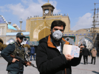An Iranian voter wears a mask and shows his ID during parliamentary elections at the Shah Abdul Azim shrine on the southern outskirts of Tehran on February 21, 2020. - Iran's health ministry today reported two more deaths among 13 new cases of coronavirus in the Islamic republic, bringing the …