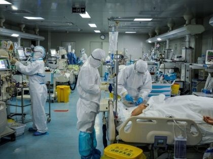 This photo taken on February 24, 2020 shows medical staff treating patients infected by the COVID-19 coronavirus at a hospital in Wuhan in China's central Hubei province. - The new coronavirus has peaked in China but could still grow into a pandemic, the World Health Organization warned, as infections mushroom …