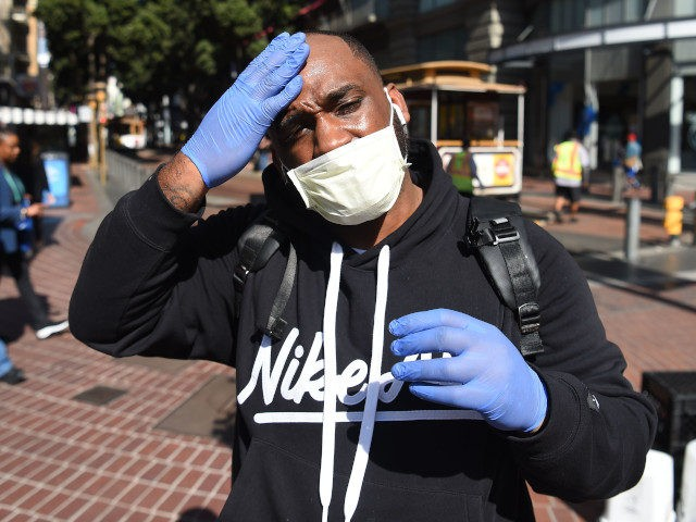 Cameron Nightingale adjusts his mask and gloves, a precaution to protect himself from coronavirus, while walking by cable car in San Francisco, California on February 27, 2020. - California said it was monitoring some 8,400 people for the new coronavirus, after officials confirmed a woman had contracted the disease without …