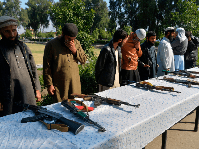 Former Afghan Taliban fighters stand next to weapons before handing them over as part of a government peace and reconciliation process at a ceremony in Jalalabad on March 1, 2020. - The United States signed a landmark deal with the Taliban on February 29, laying out a timetable for a …