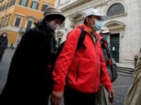 Asian tourists wearing protective masks walk past the Church of St. Louis of the French (San Luigi dei Francesi) in Rome on March 1, 2020. - The French community church closed its doors to the public on March 1, reportedly after a priest was infected with COVID-19 (novel Coronavirus). (Photo …