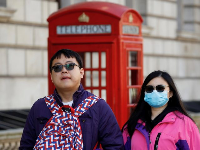 A tourist wears a surgical face mask as she walks past a red telephone box in central London on March 2, 2020. - Britain's Prime Minister Prime Minister on Monday chaired an emergency COBRA meeting on the coronavirus outbreak, after the number of confirmed cases of COVID-19 in the United …