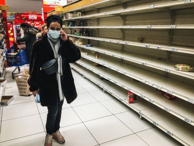 A woman with a face mask stands near empty stalls in a supermarket in the Qwartz shopping centre in Villeneuve-la-Garenne, north of Paris, on March 2, 2020. - Supermarket shelves in countries affected by the COVID-19 virus have been emptied of basic necessities, such as pasta and toilet paper, in …