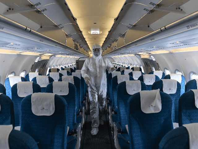 A worker wearing a protective suit disinfects a Vietnam Airlines plane amid concerns of the spread of the COVID-19 coronavirus at Noi Bai International Airport in Hanoi on March 3, 2020. - (Photo by Nhac NGUYEN / AFP) (Photo by NHAC NGUYEN/AFP via Getty Images)