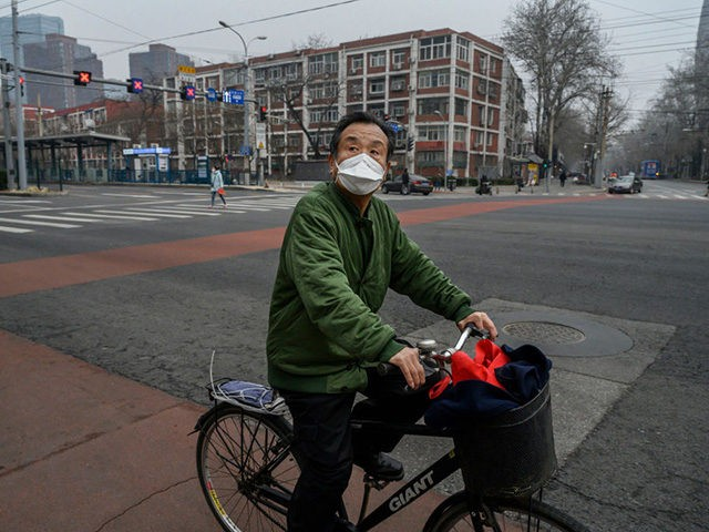 BEIJING, CHINA - MARCH 06: A Chinese commuter wears a protective mask while riding through a nearly empty intersection during the afternoon rush hour on March 6, 2020 in Beijing, China. The number of cases of the deadly new coronavirus COVID-19 being treated in China dropped to below 26,000 in …
