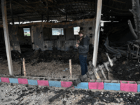 A volunteer teacher takes pictures on March 8, 2020 in the rubbles of the school building of a One Happy Family, a Swiss-operated family care centre for refugees just outside the island of Lesbos capital Mytilene, a day after it burns following violence as Greece announced further restrictions towards asylum …