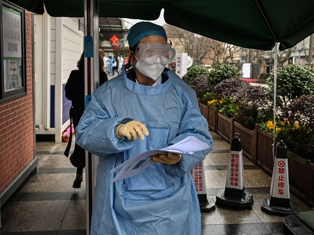 A medical worker wearing protective clothing as a preventive measure against the COVID-19 coronavirus, stands at the entrance of Xuhui District Hospital in Shanghai on March 9, 2020 - China reported 22 new deaths on March 9 from the new coronavirus epidemic, and the lowest number of fresh cases since …