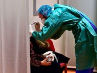 A doctor examines a patient at the hospital screening unit of the CHU Pellegrin in Bordeaux, southwestern France on March 9, 2020. - The CHU Pellegrin in Bordeaux has opened a screening unit for the novel coronavirus where patients are examined in a box by a team made up of …