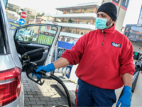 A petrol station employee wearing a respiratory mask as part of precautionary measures against the spread of the new COVID-19 coronavirus, fills a car's tank in Rome on March 10, 2020. - Italy imposed unprecedented national restrictions on its 60 million people on March 10, 2020 to control the deadly …