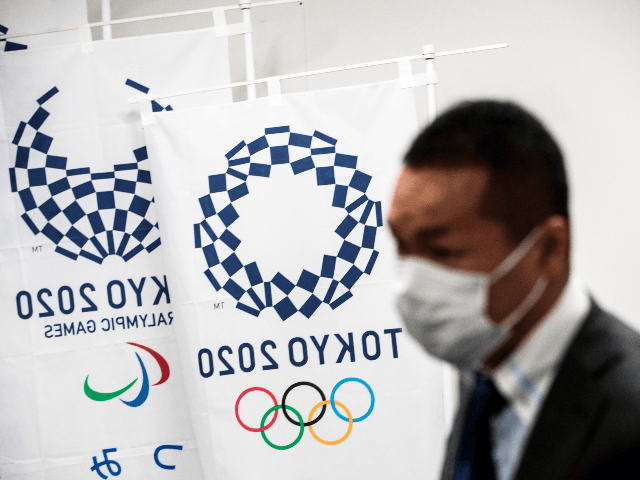 """A reporter wearing a face mask stands next to the banners of the Tokyo Olympic Games during a Tokyo 2020 press conference about the spread of the new coronavirus in Tokyo on March 11, 2020. - Preparations for the Tokyo 2020 Olympics this summer are going ahead """"as scheduled,"""" organisers …"""