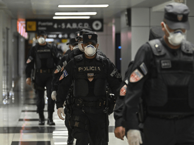Members of the Police's Maintenance Unit at San Oscar Romero International Airport in San Luis Talpa, El Salvador, wear face masks as a precaution against the spread of the new coronavirus, the COVID-19, on March 12, 2020. - El Salvador banned entry to all foreigners for a period of 21 …