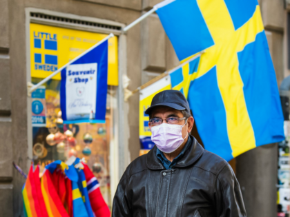 A toursit wears a protective face mask as he visits the old town in Stockholm on March 13, 2020. (Photo by Jonathan NACKSTRAND / AFP) (Photo by JONATHAN NACKSTRAND/AFP via Getty Images)