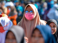A woman wears a face mask at a public space in Banda Aceh on March 14, 2020. - As of March 13, there were over 140,000 confirmed cases of the COVID-19 illness in 124 countries, with more than 5,000 deaths. (Photo by CHAIDEER MAHYUDDIN / AFP) (Photo by CHAIDEER MAHYUDDIN/AFP …