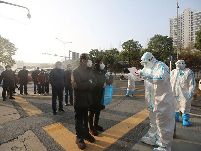 Medical workers (R) check patients who recovered from the COVID-19 coronavirus as they arrive to be tested again at a hospital in Wuhan, in China's central Hubei province on March 14, 2020. - China reported 11 new infections of the coronavirus on March 14, and for the first time since …